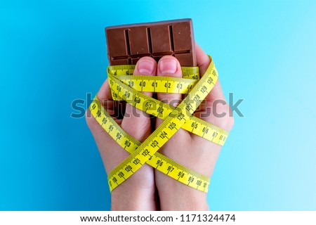 Diet concept. Losing weight concept. Chocolate in the hands tied with yellow measuring tape on a blue background.