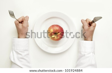 Diet concept. Male hands holding cutlery between plate with an apple.
