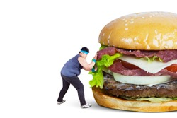 Diet concept. Overweight man wearing sportswear while pushing big burger, isolated on white background