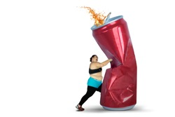 Diet concept. Overweight woman punching a can of soft drink. Isolated on white background
