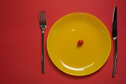Diet concept plate top view. Cherry tomato on yellow empty plate with fork and knife on red background