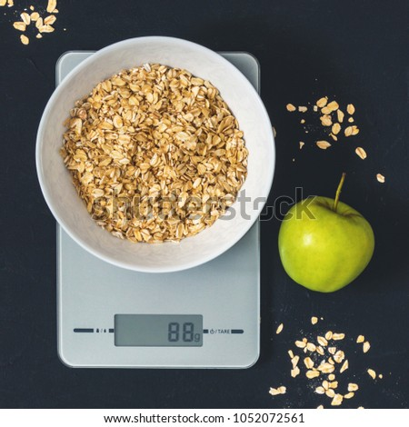 Diet concept, proper nutrition, healthy eating. Oatmeal in a white plate on the kitchen scale. Weighing products. Breakfast, Top View
