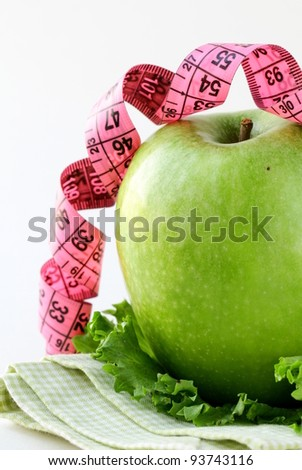 Diet concept Ripe green apple with measuring tape