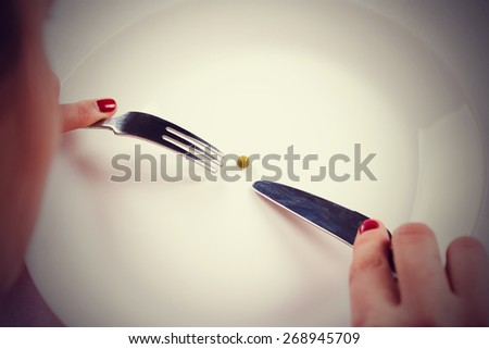 Woman Holding Knife And A Fork With One Bean On White Table