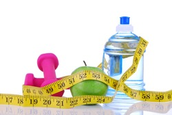 Diet diabetes weight loss concept with tape measure organic green apple, pink dumbbels and natural bottle of sparkling water on a white background. Focus on water
