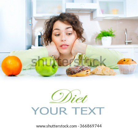 Diet. Dieting concept. Healthy Food. Beautiful Young thinking Woman choosing between Fruits and Sweets. Weight Loss