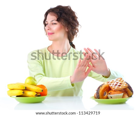 Diet. Dieting concept. Healthy Food. Beautiful Young Woman choosing between Fruits and Sweets. Isolated on white