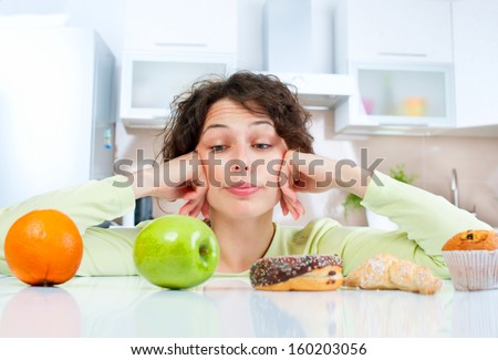 Shutterstock Diet. Dieting concept. Healthy Food. Beautiful Young Woman choosing between Fruits and Sweets. Weight Loss