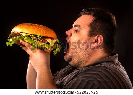 Diet failure of fat man eating fast food hamberger. Breakfast for overweight person who spoiled healthy food by eating huge hamburger. Junk meal leads to obesity. Person regularly overeats concept . ストックフォト ©