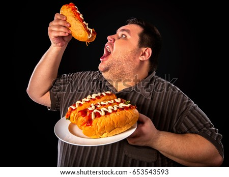 Diet failure of fat man eating fast food hot dog on plate. Breakfast for overweight person who greedily eats lot . Junk meal leads to obesity. Enraged by large amount of food fat. ストックフォト ©