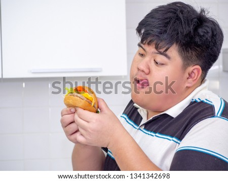 Diet failure of fat man eating fast food unhealthy hamberger. #1341342698