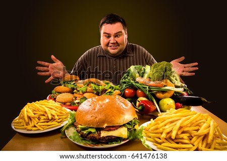 Diet fat man who makes choice between healthy and unhealthy food. Overweight male with hamburgers, french fries and vegetables trays trying to lose weight first time Dinner is field of the working day ストックフォト ©