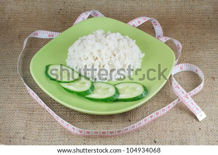 diet food. A handful of rice and cucumbers on the green plate on a rough burlap cloth