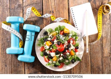 diet food concept, vegetable salad and dumbbel