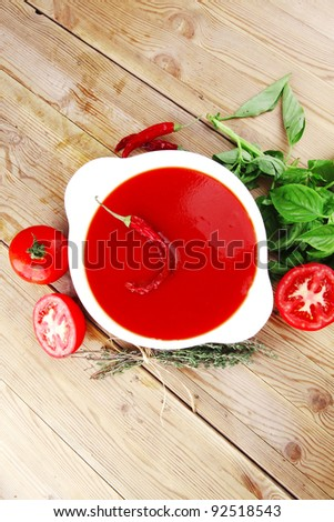 diet food : hot tomato vegetable soup with basil thyme and raw tomatoes in white round bowl over red mat on wood table ready to eat