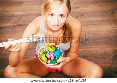 Diet, healthy eating, weight loss and slim body concept. Fit fitness girl holding bowl with many colorful measuring tapes