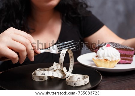 Diet, healthy eating, weight loss and slim body concept. Overweight girl with fork choosing slimness instead of sweets