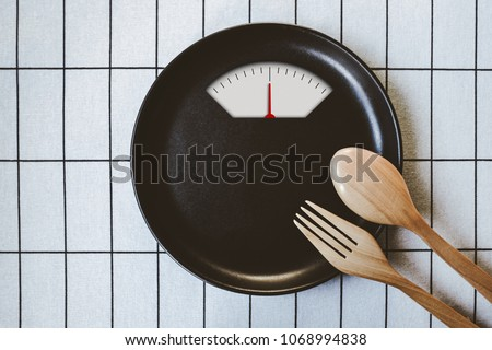 Diet menu. Top view of black plate with weight scale and wooden spoon and fork, Time to diet concept, No meal, with blank copy space, minimal Japanese style