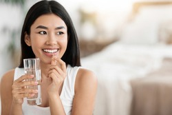 Diet, nutrition, healthy eating concept. Close Up Of Happy Smiling Asian Woman Taking Supplement Pill And Holding Glass Of Fresh Water In Morning, copy space
