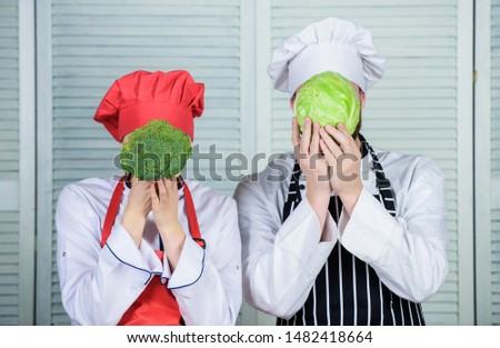 Diet on their mind. Couple cooks hold cabbage and broccoli in front of face. Healthy food concept. Couple cooking healthy vegetarian meal. Vegetarian family. Vegetarian nutrition and vegetable diet.