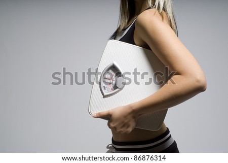Diet or dieting scale concept held by slim, healthy or trim woman
