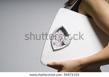 Diet or dieting scale concept held by slim, healthy or trim woman close up