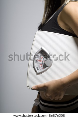 Diet or dieting scale concept held by slim, healthy or trim woman portrait shape