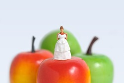 Diet plan before wedding or marriage day concept. Woman standing above apple with trying wedding dress. Miniature people, toys photography.
