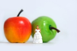 Diet plan before wedding or marriage day concept. Woman standing in front of apple with trying wedding dress. Miniature people, toys photography.