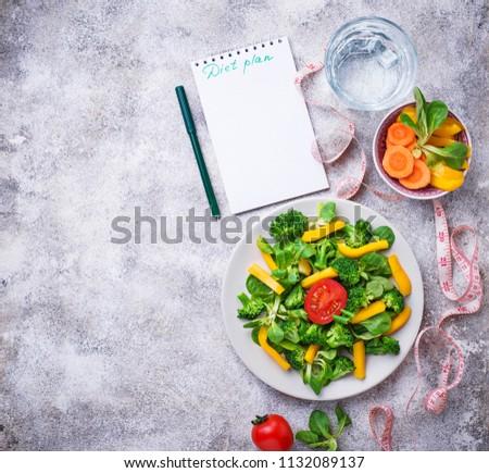 Diet plan. Healthy vegetable salad, clean water and measuring tape. Top view #1132089137