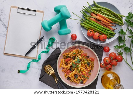 Diet plan, menu or program, tape measure, water, dumbbells and diet food, top view. Vegetarian vegetable pasta. Tasty appetizing classic italian spaghetti pasta with tomato sauce. salad. clipboard Stock photo ©