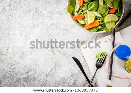 Diet plan weight lose concept, fresh vegetable salad with fork, knife, note pad,  grey stone table copy space top view #1063859375
