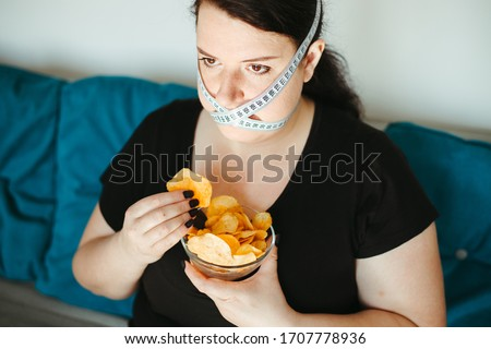 Diet restricts, weight loss, eating disorder. Anorexia and bulimia concept. Obese woman with unhealthy food, mouth closed with measure tape. Food addiction fighting Сток-фото ©