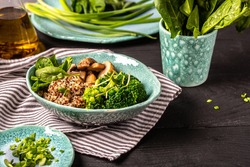 Diet salad made from fresh vegetables broccoli, mushrooms, spinach and quinoa in a bowl. Delicious breakfast or snack, Clean eating, dieting, vegan food concept. vertical image.