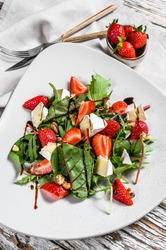 Diet salad with brie cheese, strawberries, nuts, chard and arugula. White background. Top view