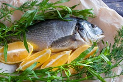 Diet sea gilthead fish prepared for roasting with lemon and herbs