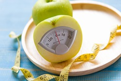 Diet slimming loss. Green apple fruit with weight scale and measuring tape for obesity body healthy. Diet and Healthy Concept.