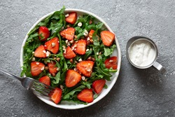 Diet summer strawberry salad with arugula on the table. Copy space, top view.