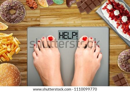Diet temptation or hard to lose weight concept with woman weighing on bathroom scale with many sweets and fast food around