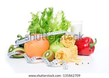 Diet weight loss breakfast concept with tape measure organic green and red pepper, tomatoes, almonds, fresh salad, spaghetti, grapefruit, glass of kefir on a white background