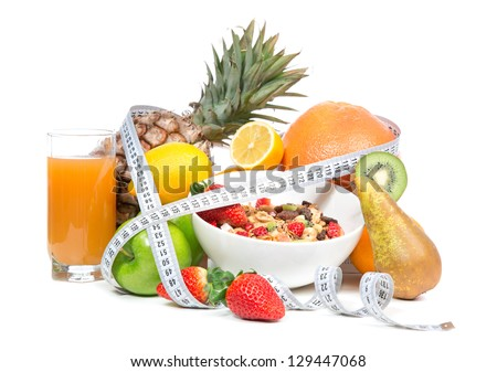 Diet weight loss breakfast concept with tape measure organic green apple, cereal bowl, orange juice, pineapple, muesli cereal bowl, pear, kiwi, lemon, strawberries on a white background