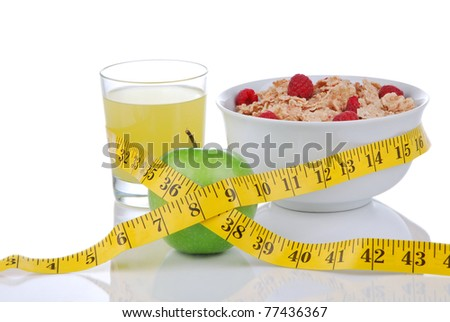 Diet weight loss concept with tape measure green and organic green apple, corn healthy rice and wheat flakes with fresh raspberries and carrot juice on a white background