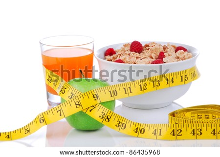Diet weight loss concept with tape measure natural green apple, corn healthy flakes with fresh raspberries and carrot juice breakfast on a white background