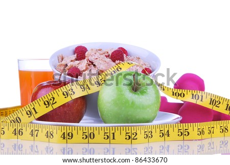 Diet weight loss concept with tape measure red and organic green apple, corn healthy rice and wheat flakes with fresh raspberries and carrot juice on a white background