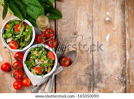 Dietary food background vegetable salad with spinach cherry tomatoes barley porridge and olive oil on an old wooden board vegan cuisine