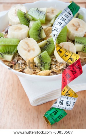 Dietary foodstuff. Plate of muesli with fresh fruits and centimeter - stock photo