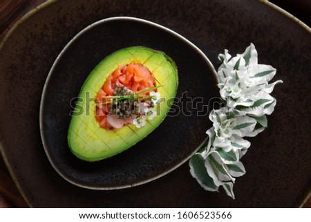 Dietary, nutritious dish, avocado with salmon, shrimp and black caviar. Quick and Easy Recipes