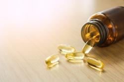 Dietary supplement cod liver oil omega 3 gel capsules. pills spilling out of prescription bottle on table background.