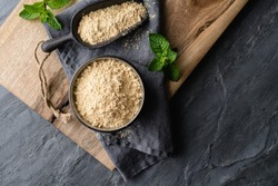 Dietary supplement, Maca root powder in a bowl and scoop on stone background with copy space