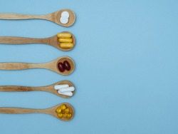 Dietary supplements and vitamins on wooden spoons on a blue background with space for text, top view, flat lay. The concept of a healthy lifestyle, taking care of your health. Vitamin b, c, e, zinc